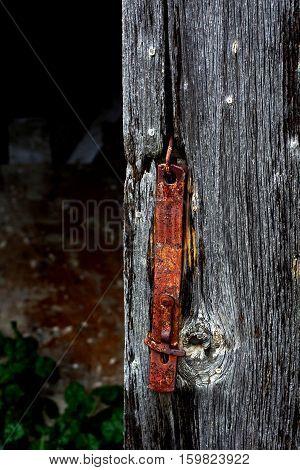 Rusty metal barn door latch on old barn wood