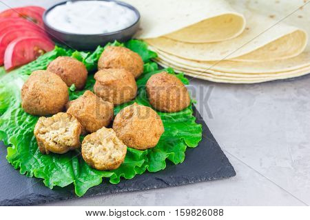 Chickpea falafel balls on slate board with vegetables and sauce horizontal copy space