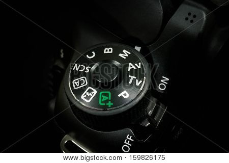 Control dial on a DSLR camera, close up image isolated on black background