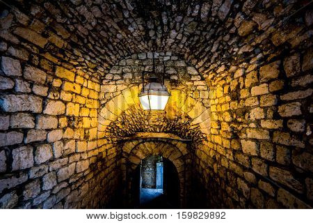 Stone passage with lamp glowing yellow and distant exit