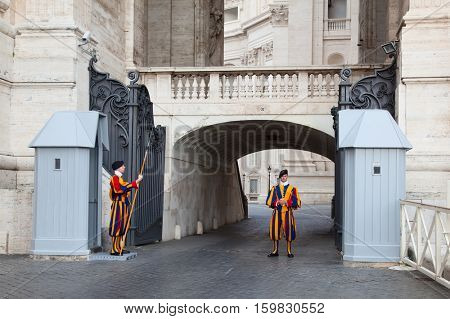 VATICAN CITY, VATICAN - AUGUST 1: Famous Swiss Guard surveil basilica entrance on August 1, 2014 in Vatican. The Papal Guard with 110 men is the world's smallest army.