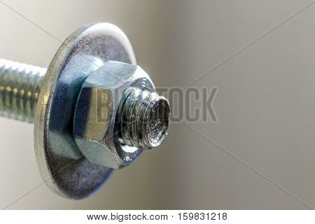 Stainless steel bolts and nuts on a white background. Bolt washer and nut on a white background. Bolt on a white background. Bolt screw nut washer carving.