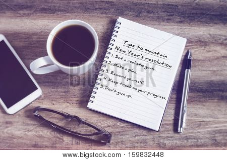 Tips To Maintain New Year's Resolution On Blank Notepad With Calculator, Coffee, Pen And Smart Phone