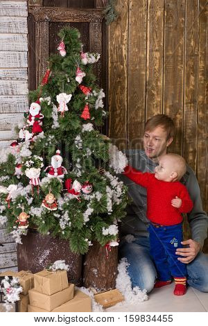 Young Father With Child Sitting In A Christmas Tree.