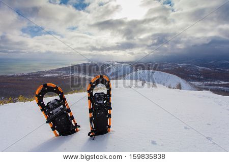 Professional snowshoes in the snow on the winter mountains background. Snowshoeing.