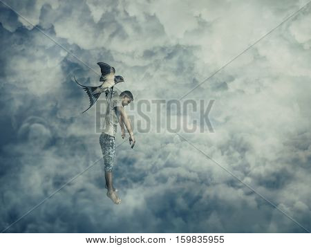 Flying bird carrying a powerless young boy hanging in her claw. Conceptual image symbolizing manipulation and control as a marionette.