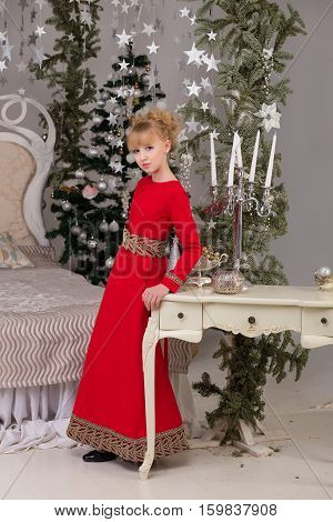 Portrait of a young beautiful blonde in a red dress at the Christmas tree. Lovely girl on the threshold of Christmas