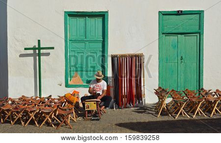 TEGUISE, LANZAROTE, SPAIN - NOVEMBER 20, 2016: Man making leather goods sitting with stools and belts for sale in front of old building.
