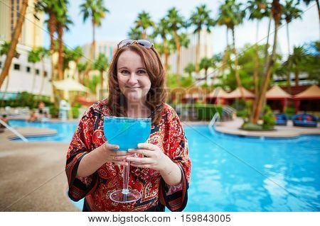 Cheerful tourist drinking a huge blue cocktail in Las Vegas Nevada USA