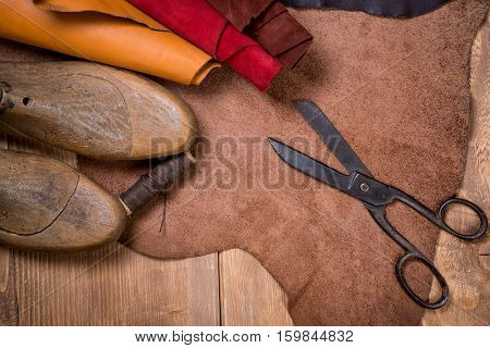 Set of leather craft tools on wooden background. Workplace for shoemaker. Piece of hide and working handmade tools on a work table.
