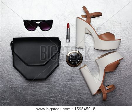 Fashion luxury female set black handbag clutch sunglasses shoes heels lipstick and little pocket mirror over textured silver background flat lay