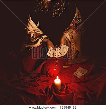 Fortune Teller Sees In The Future By Playing Her Tarot Cards In Dark With Burning Candle