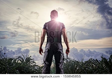 Man in headgear and black military uniform standing with gun on sunny sky background