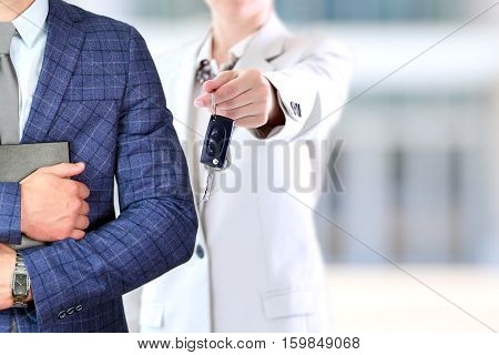 Successful businesswoman offering a car key.Business man holding documents behind. Car rental.