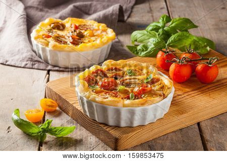Quiche with cherry tomatoes on a rustic wooden table.