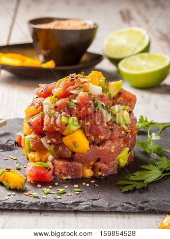 Hawaiian tuna poke with mango avocado onion and sesame seeds.