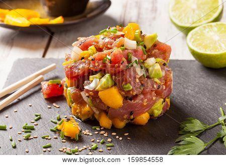 Hawaiian tuna poke with mango avocado onion and sesame seeds. poster