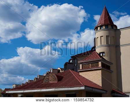 Beautiful roof of the house against the sky with cumulus clouds