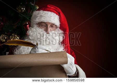 Santa Claus writing on old paper roll list with quill pen