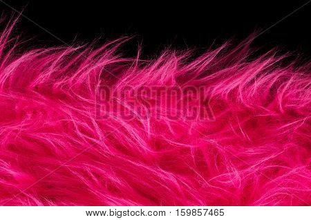 Pink plush fabric on black background horizontal. Very soft polyester textile made of synthetic fibers with long hairs. Macro close up material photography, front view.