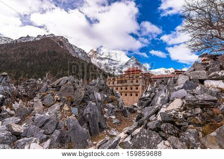 Tibetan temple on the snow mountain with gray rocks in Yading Nature Reserve China in dark and light tone.