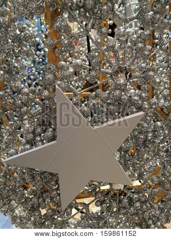 Embellished Christmas decoration star and white glitter silver tinsel background