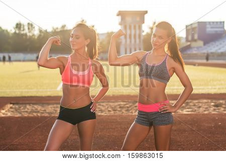 Sporty young women with perfect bodies showing biceps