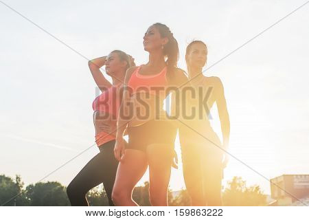 Group of fit young sportswomen standing in athletics stadium and posing