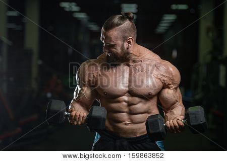 Brutal Strong Bodybuilder Athletic Men Pumping Up Muscles With Dumbbells