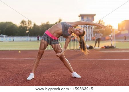 Fit woman doing side bend stretching exercise warming up