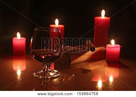 christmas composition photo cognac glass and candle on black background.