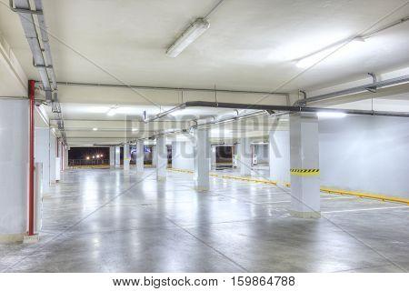 Underground garage. Empty light underground parking garage