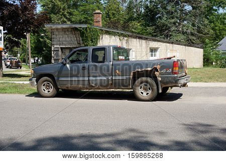 HARBOR SPRINGS, MICHIGAN / UNITED STATES - AUGUST 3, 2016: A 4x4 pickup truck is parked outside of a construction site on Traverse Street in Harbor Springs.