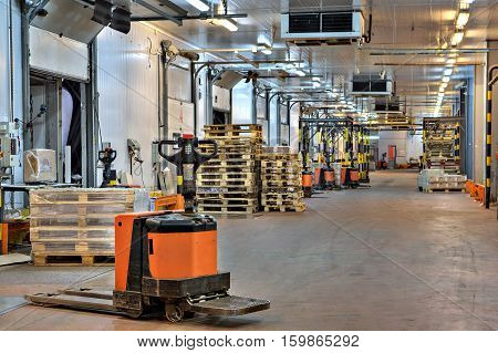 Saint-Petersburg Russia - October 31 2016: electric platform pallet truck in loading dock area inside cold storage warehouse.