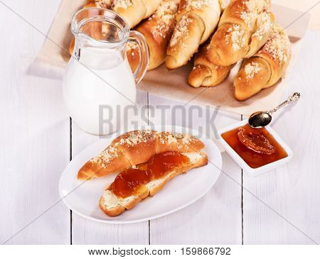 Croissant with peach jam and milk on a white background fresh bakery