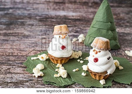 Christmas sweets. Two meringue cakes in the form of snowman, popcorn balls, a green paper napkin, folded in the form of a Christmas tree, on an old wooden table.