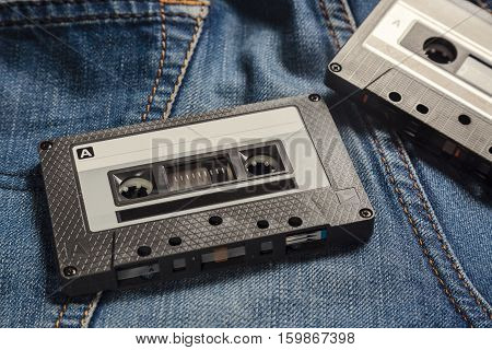 Audio Tape Cassettes on the blue jeans. Vintage toned image