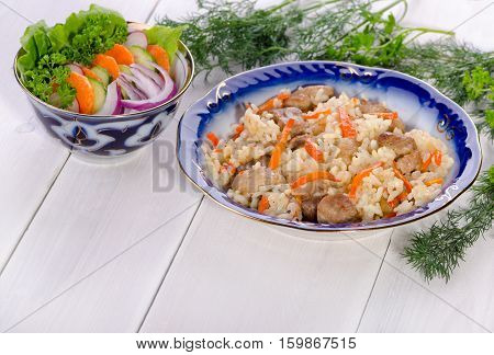 Pilau rice with meat and vegetables on a white wooden table with fresh herbs