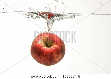 Splashing red apple on clear water and white background