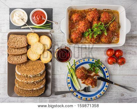 Delicious meal rich in protein and vitamins. Meatballs with tomato sauce, tomatoes, bread, mayonnaise, ketchup and a glass of wine on a white wooden background. Top view