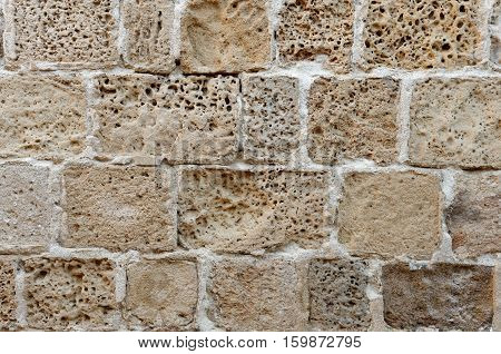 Wall built of rough weathered sandstone blocks