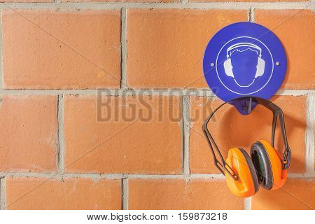 an blue placard for compulsory wearing of ear protection and a hearing protector on the hook poster