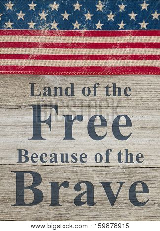 USA patriotic message USA patriotic old flag on a weathered wood background with text Land of the Free Because of the Brave