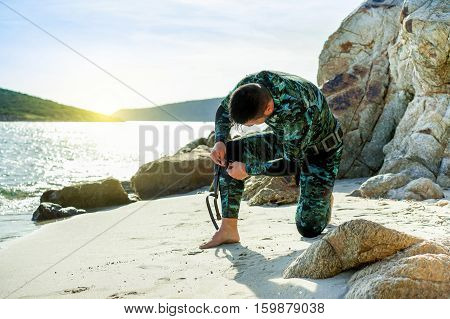 Male hunter getting ready for hunting in mediterranean sea - Young man preparing his knife for underwater fishing - Extreme sport concept - Focus on his head - Warm filter with sun flare