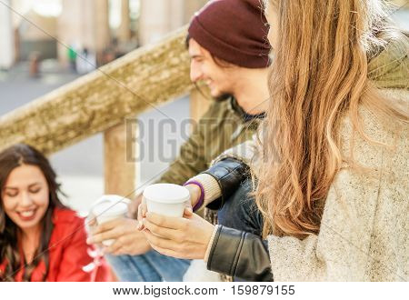 Young people toasting coffee in paper take away cup in staircase city center outdoor - Three friends having break drinking cappuccino - Winter concept - Focus on woman hand - Warm filter