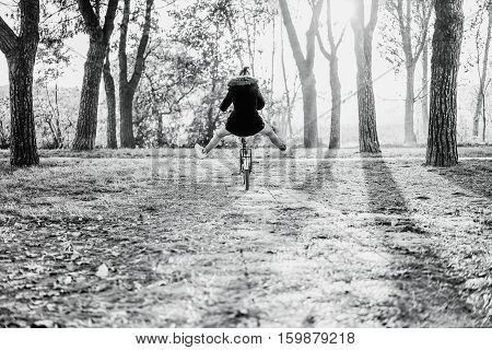 Woman riding vintage old italian style bicycle with her legs in the air - Girl having fun in park outdoor with back light - Freedom concept - Black and white editing - Warm vintage retro filter