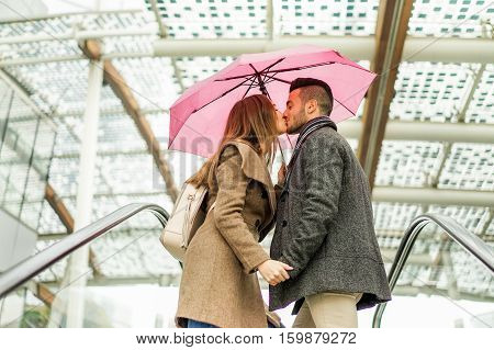 Two lovers kissing each others on mall shopping centre escalator - Young couple having tender moments under the rain in city urban center - Love concept - Warm filter - Focus on man