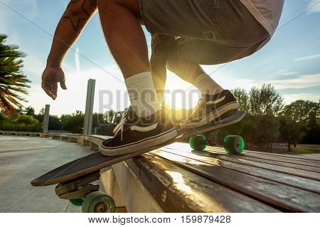 Silhouette of young man perfoming with skateboard up wood bench at sunset in urban city park - Skater having fun with back sunlight - Extreme sport concept - Focus on left shoe - Warm filter