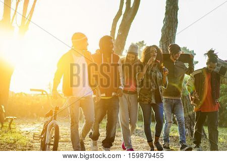 Group of cheerful friends walking and chatting in city park with back light - Friendship concept with multicultural young people having fun together - Focus on left man face - Warm filter