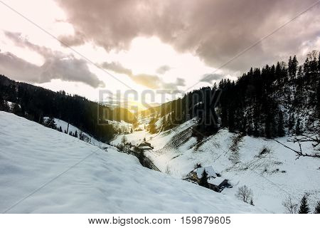 Panoramic view of Langnau in Emmental valley in Switzerland Bern region - Winter natural landscape - Focus on houses - Vintage sun flare color tones filter